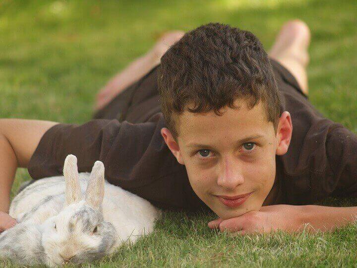 Pojke med kanin ligger pa gront gras